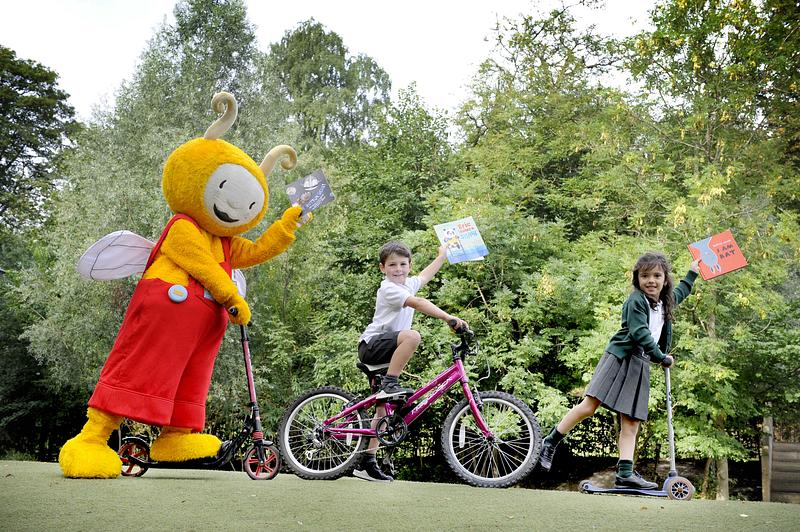 Bookbug and children riding bikes and scooters with the Bookbug Picture Book Prize shortlisted books