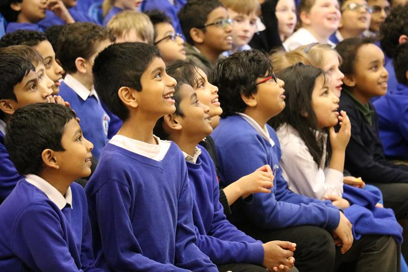 Children in a school watching an author event