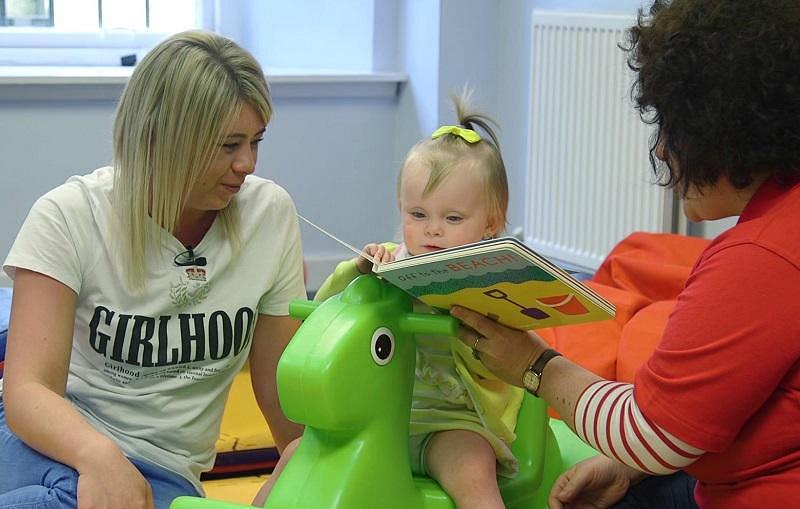 Mum and support worker read to a little girl