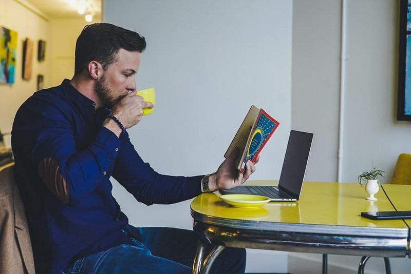 Man sitting at a desk reading a book and drinking a cup of tea