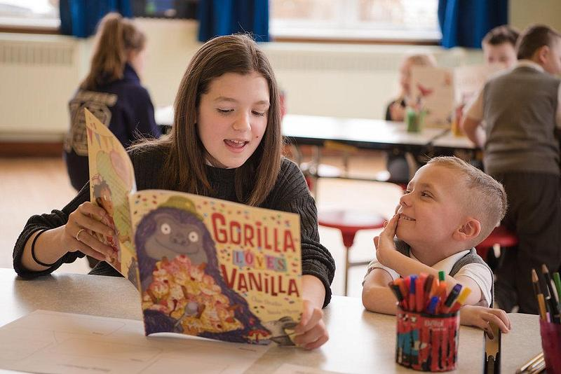 Girl reading 'Gorilla Loves Vanilla' to a young boy