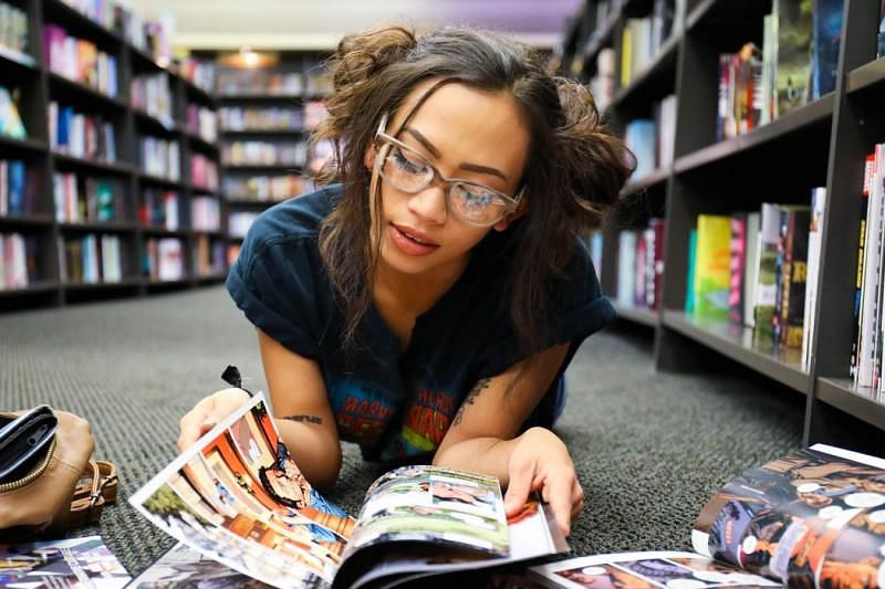 A teenager lying on the floor of a library reading a comic book
