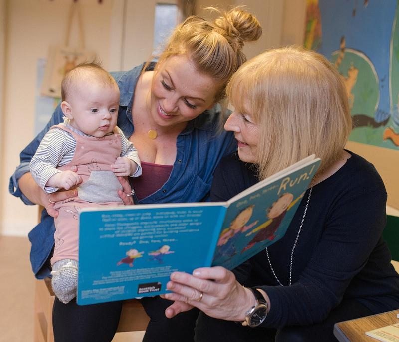 Two women reading a picture book with a baby