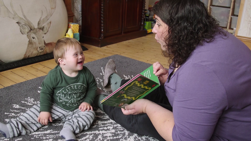 A woman reading a picture book with a toddler