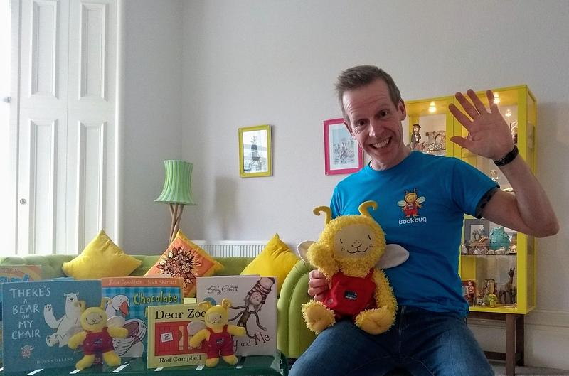 Session Leader holding Bookbug doll, surrounded by books
