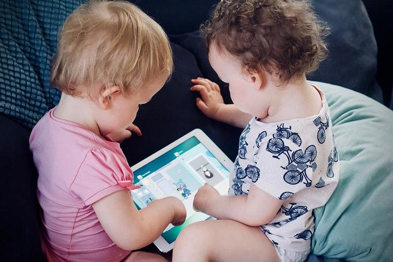 Two young children playing on a tablet
