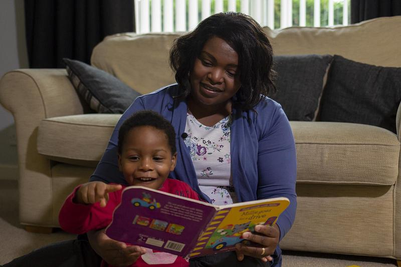 A woman and toddler reading a picture book together