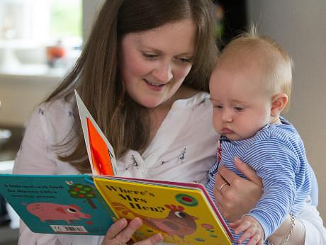 Woman reading 'Where's Mrs Hen' to her baby