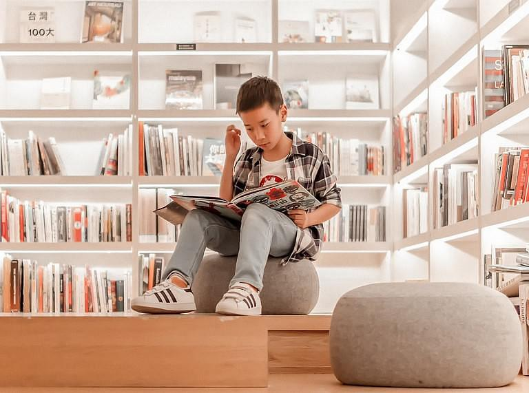 Child sat reading a book, surrounded by book shelves