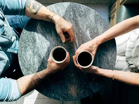 Two people sat at a table holding cups of coffee